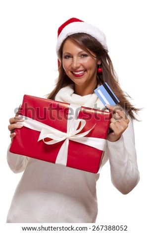 Attractive woman with a lovely smile wearing a red Santa hat holding a big red Christmas gift box and bank card as she celebrates her successful shopping spree - stock photo