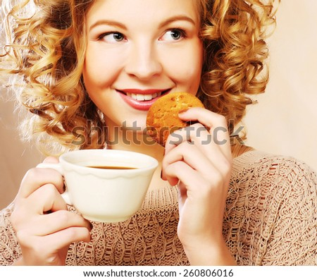 attractive woman with coffee and cookies, studio shot - stock photo