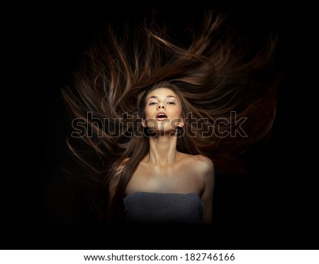 Attractive woman with flying hairs on black background - stock photo