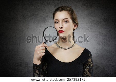 Attractive woman with magnifying glass - stock photo