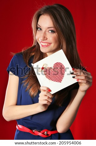 Attractive woman with postcard, on red background - stock photo