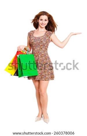 attractive woman with shopping bags and offering gesture on isolated background - stock photo