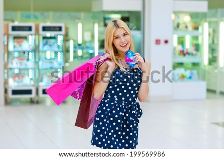 attractive woman with shopping bags holding credit card - stock photo