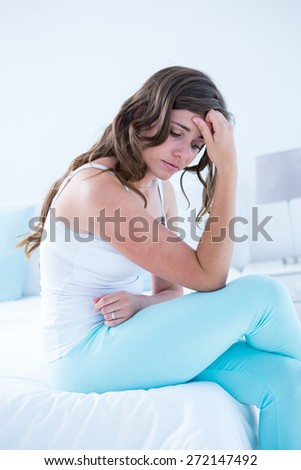 Attractive woman with stomach pain at home in the bedroom - stock photo