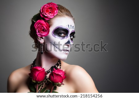 attractive woman with sugar skull make up  - stock photo