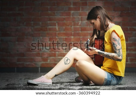 Attractive woman with tattoo playing guitar on brick background - stock photo