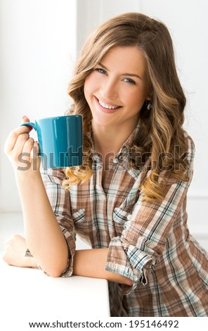 Attractive woman with tea cup - stock photo