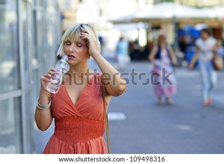 attractive woman with water bottle in the city - stock photo
