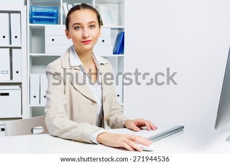 Attractive woman working in office on computer - stock photo