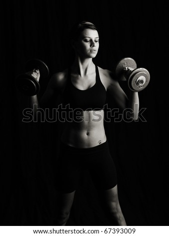 Attractive woman working out. Low key studio shot on black