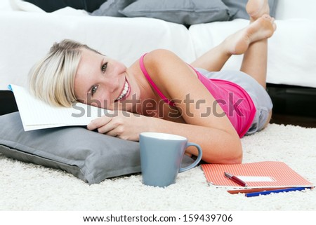 Attractive woman writing a note in the living room.