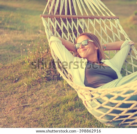 attractive woman 30 years old in a hammock. Outdoor. Image with retro filter - stock photo