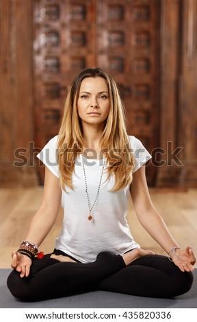 Attractive woman yoga trainer in lotus (padmasana) pose - stock photo