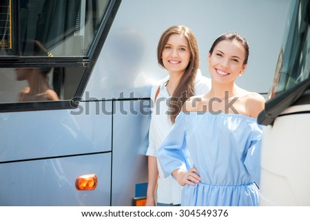 Attractive women are enjoying their trip. They are standing near a public transport. The friend are looking at the camera with joy and smiling - stock photo
