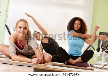 Attractive women doing stretching exercises at the gym after workout. - stock photo