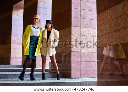 Attractive women in hats stand straight between the pillars