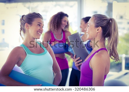 Attractive women looking at each other and smiling while holding exercise mat in fitness studio