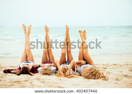 Attractive women lying down on the beach and putting their feet up. - stock photo