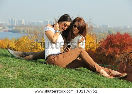 attractive women with autumn maple leaves in park at fall outdoors - stock photo