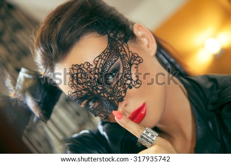 Attractive women with black lace mask. Shallow depth of field. Selective focus. - stock photo