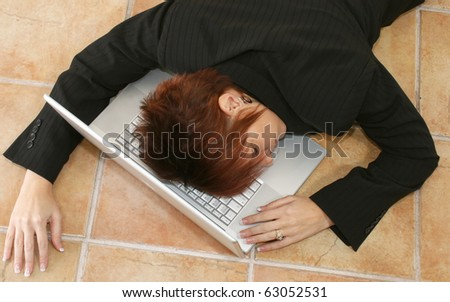 Attractive 30 year old business woman in suit asleep on laptop on office floor. - stock photo