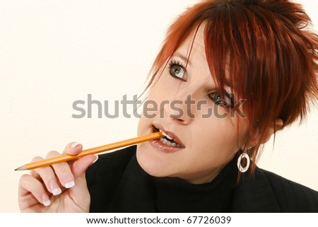 Attractive 30 year old business woman with pencil in mouth thinking. With eyeglasses. - stock photo