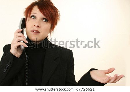 Attractive 30 year old frustrated woman on landline telephone in suit.