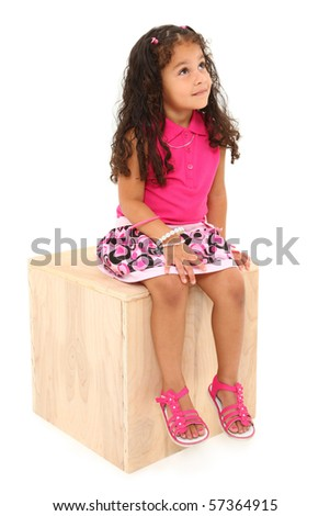Attractive 3 year old mixed race american girl sitting on wooden block day-dreaming over white background. - stock photo