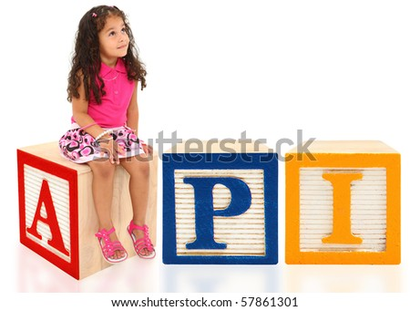 Attractive 3 year old mixed race american girl sitting on wooden block spelling API. - stock photo