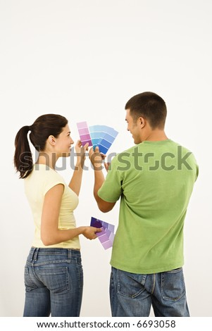 Attractive young adult couple holding color paint samples up to white wall.