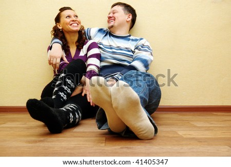 Attractive young adult couple sitting on hardwood floor in home smiling and laughing. - stock photo