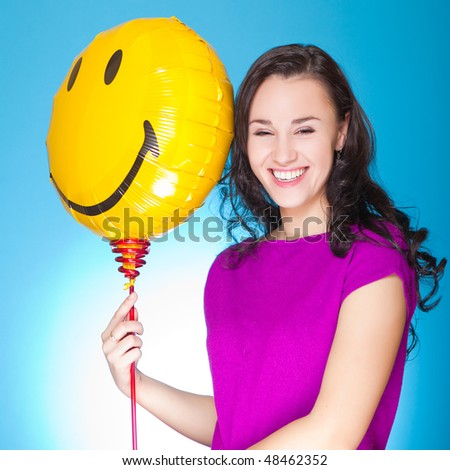attractive young adult holding a balloon in shape of smiley isolated on blue - stock photo