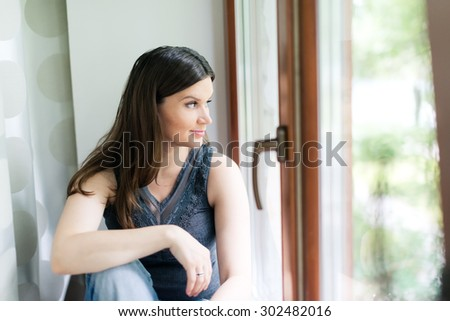 attractive young adult looking at the window  - stock photo