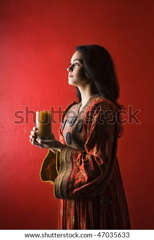 Attractive young adult woman in cultural dress, standing against red wall and holding a candle. Vertical shot. Isolated on red.