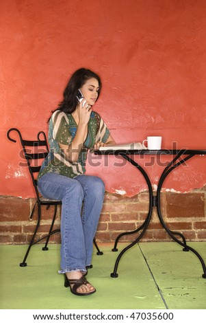 Attractive young adult woman sitting in front of a colorful wall. She is reading a book and talking on a cellphone. Vertical shot.