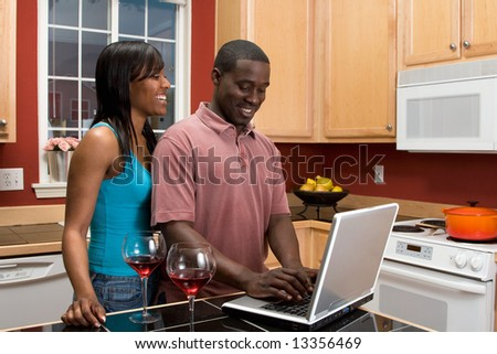 Attractive young African american couple laughing together in their kitchen while looking at something on a computer screen.