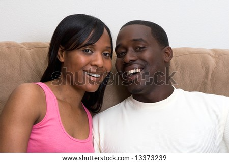Attractive young african american couple sitting together on their living room couch. Zoomed in Horizontally framed shot. The couple are looking at the camera and laughing.