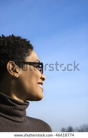 Attractive young African American woman in glasses smiles and looks out to the side during a sunny blue day. Vertical shot.