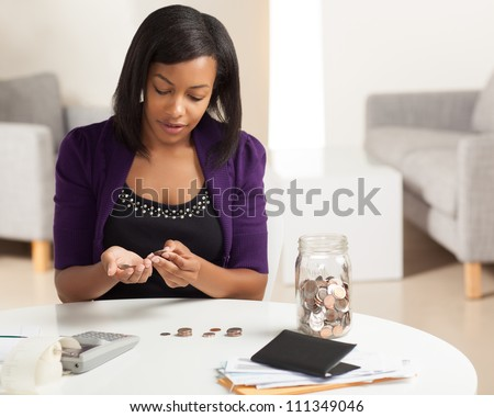 Attractive young African American woman working on finances at home wearing purlple jacket sitting at dining table. - stock photo
