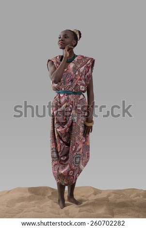Attractive young African fashion model woman standing on sand on gray studio background - stock photo
