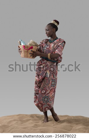Attractive young african woman holding basket with goods standing on sand on gray studio background - stock photo