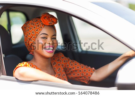 attractive young african woman in a car - stock photo