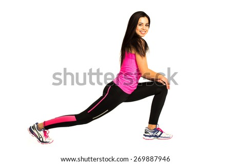 Attractive, young and fit woman smiling into the camera and stretching her legs with shadows over a white background - stock photo