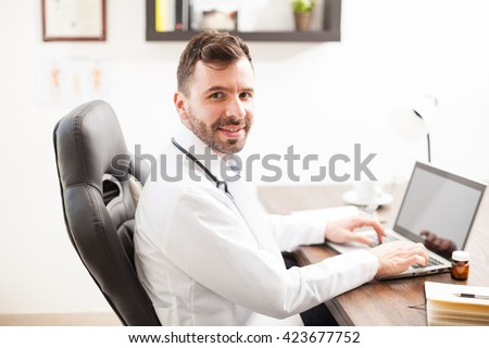 Attractive young and friendly Latin physician doing some work in a laptop computer in his office - stock photo