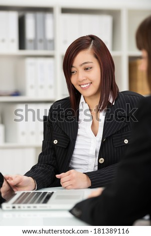 Attractive young Asian businesswoman working with a female colleague in the office as they share a laptop while working as a team - stock photo
