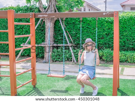 Attractive Young Asian Girl Wear Jean Sitting On Wooden Swing Swing Set Of Chain Swings