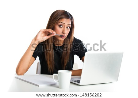 Attractive young Asian Indian teenage woman, thinking and studying on a non-branded generic laptop  - stock photo
