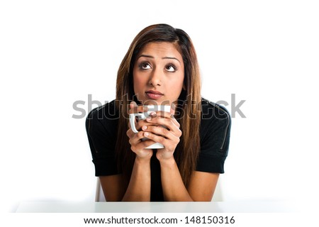 Attractive young asian indian woman thinking and enjoying a drink - stock photo
