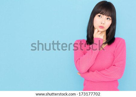 attractive young asian woman isolated on blue background - stock photo