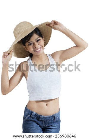 Attractive young asian woman smiling at the camera with hat on her head, shot in the studio - stock photo